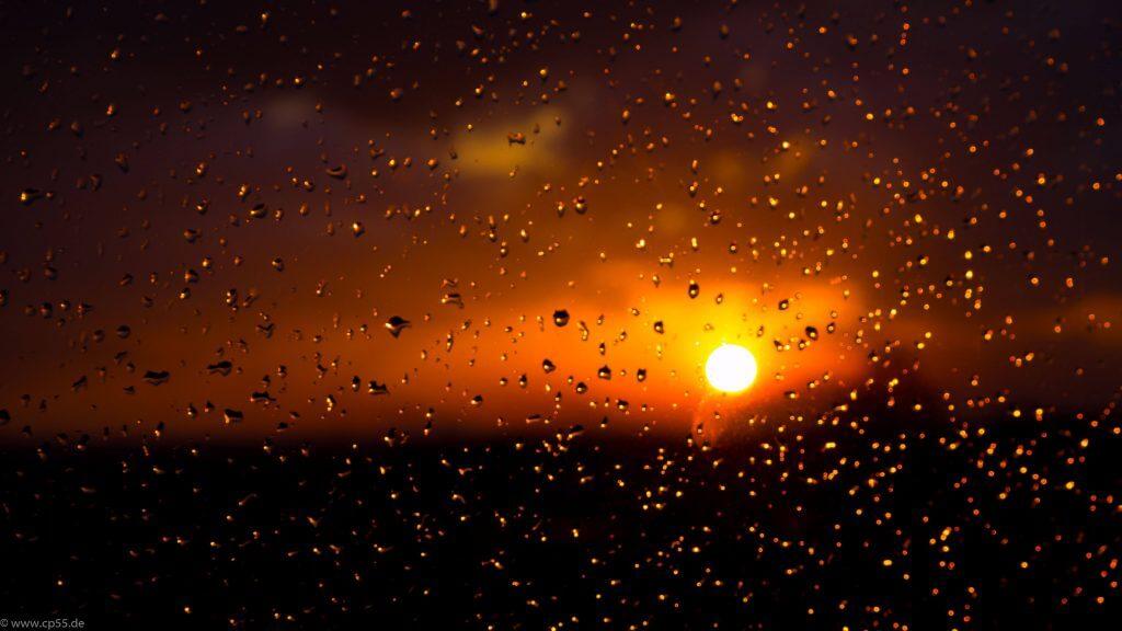 unscharfe Sonne hinter Regentropfen an der Scheibe