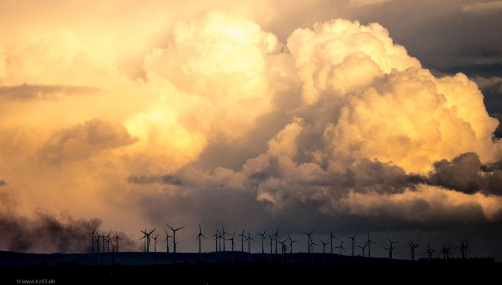Wolkenspiel hinter Windrädern und einem Osterfeuer