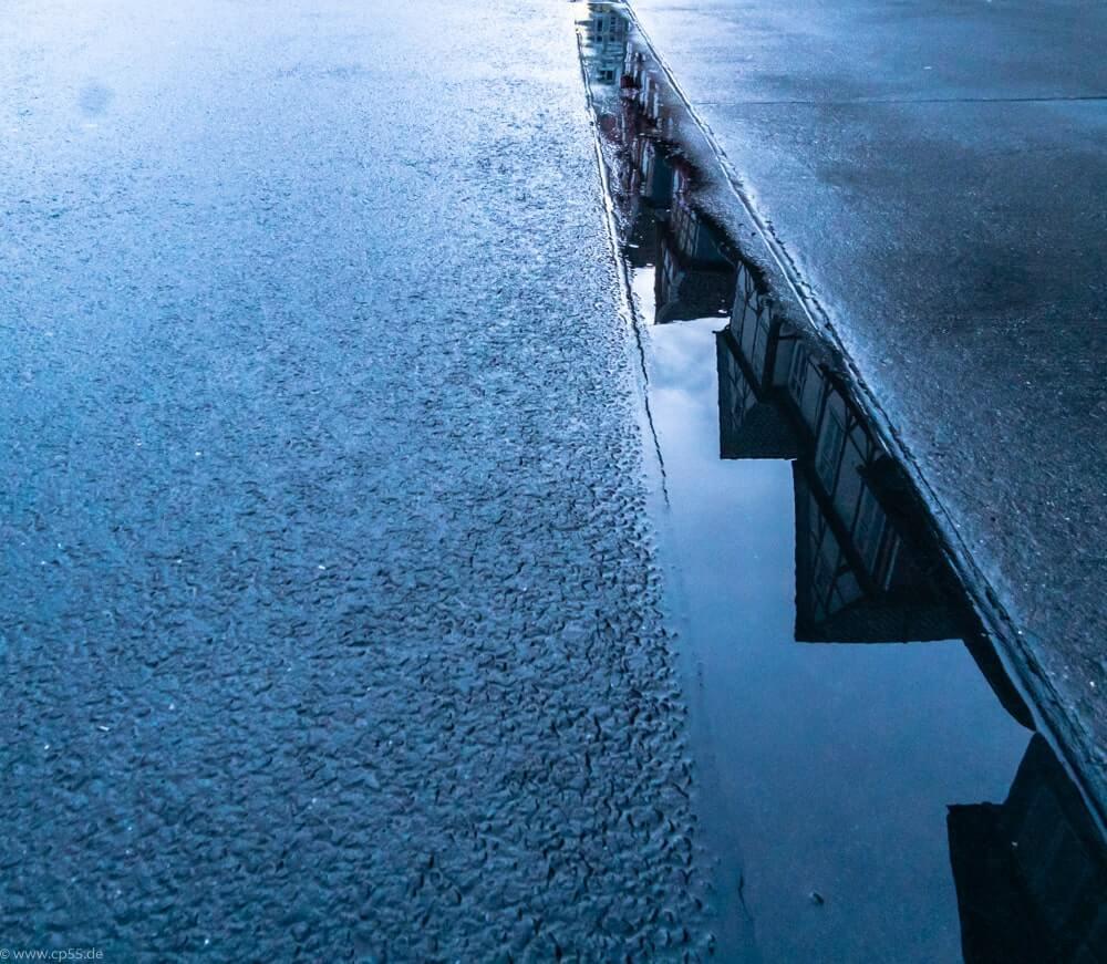 Fachwerkgiebel spiegeln sich in Pfützen zur blauen stunde