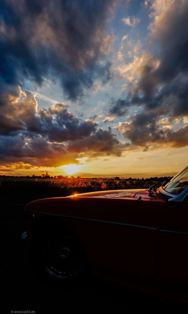 dramatischer Sonnenuntergang hinter der Motorhaube